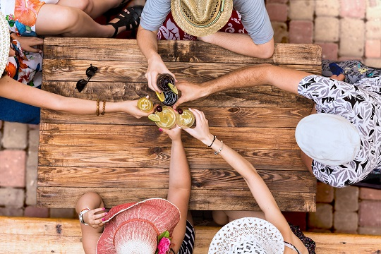 Hand of people cheers with alcohol cocktails at natural handcrafted wooden desk with brown sharp texture casual summer vacation style dress hats
