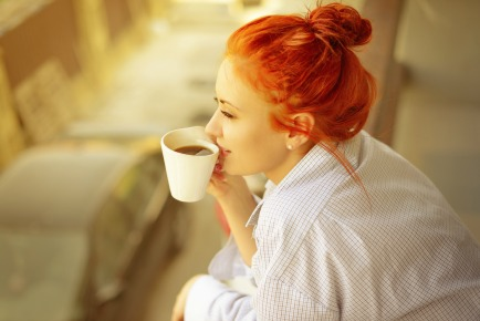 good morning womans with cup of fragrant coffee on balcony