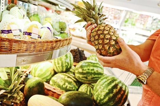 Man choosing pineapple in grocery store